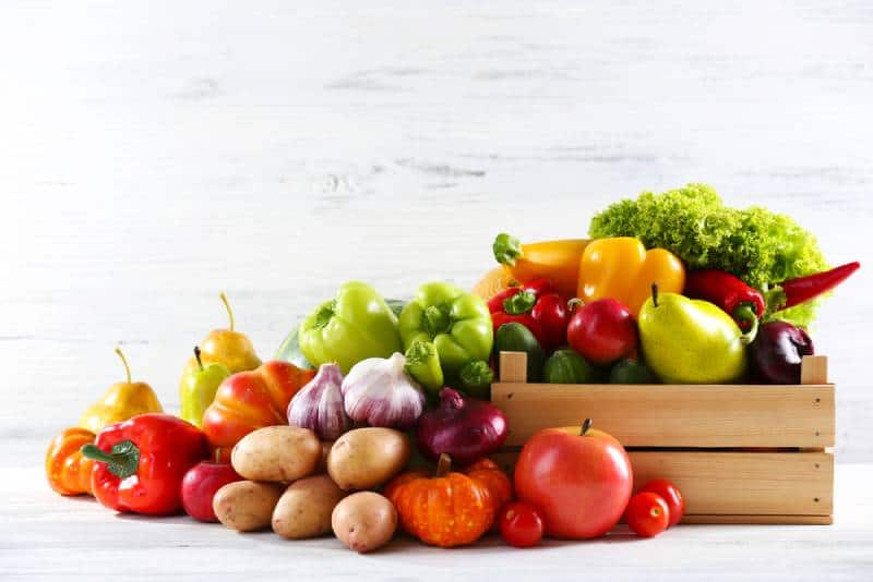 fresh fruits and vegetables on wooden background