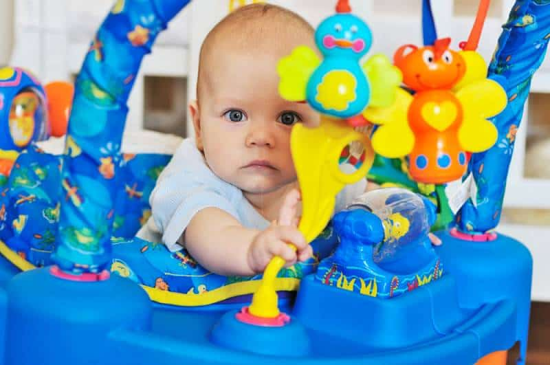 funny baby playing in baby jumper