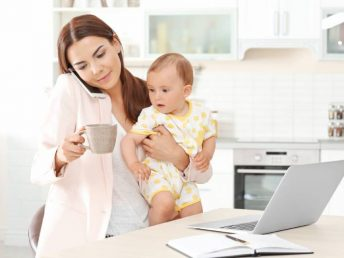 mother holding baby while talking on phone at home