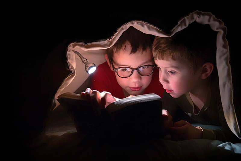 two boys reading stories for kids under blanket