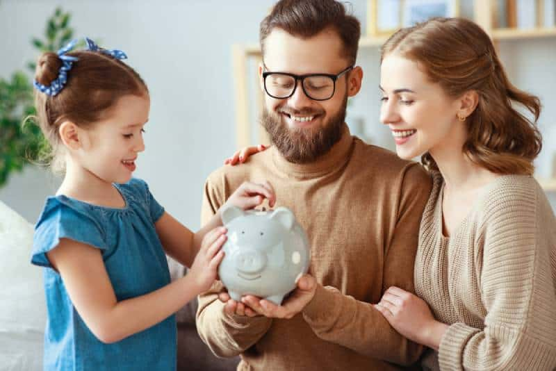 family with piggy bank money box in a living room