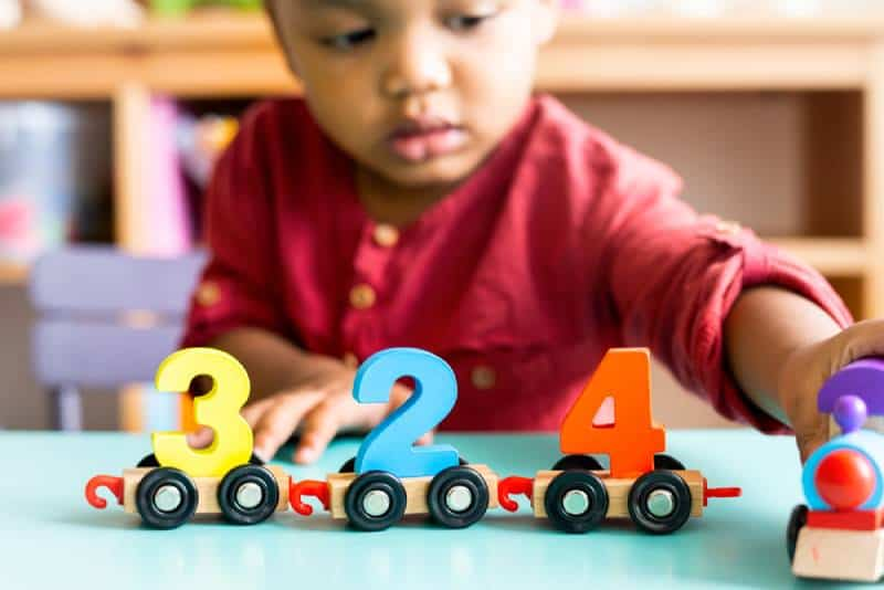 Little boy in red shirt playing mathematics wooden toy at nursery