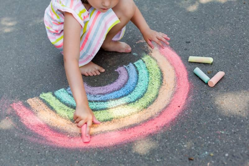 girl drawing a rainbow colored chalk on the asphalt on summer sunny day
