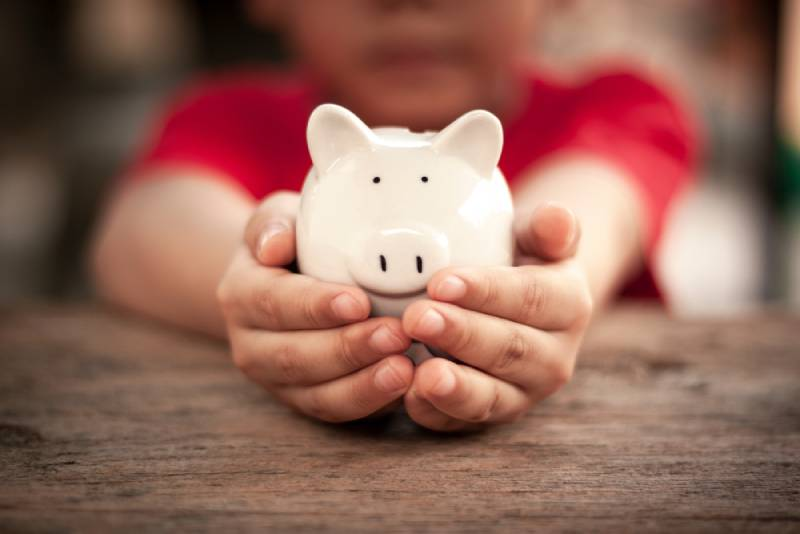 Child's hand is holding a white piggy bank on wooden table
