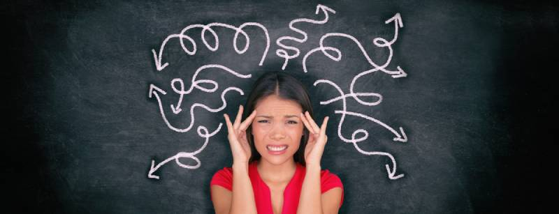 Confused woman confusion illustrated on blackboard with chalk drawing of arrows going everywhere around head showing indecision