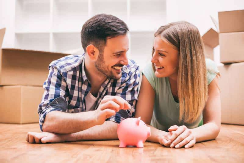 Young couple lying on floor and putting money in a piggy bank