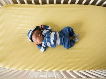 baby in crib with yellow crib sheet