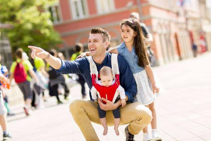 Young father walking with cute baby girl in a carrier and his another daughter on the street