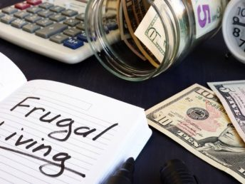 Frugal living written on a note pad, money and a calculator on a table