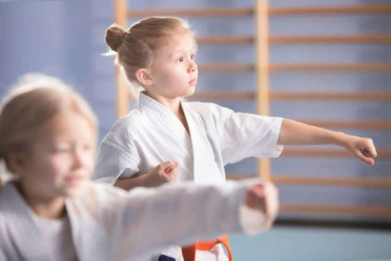 Young girls in kimono exercising during an extra-curricular karate class