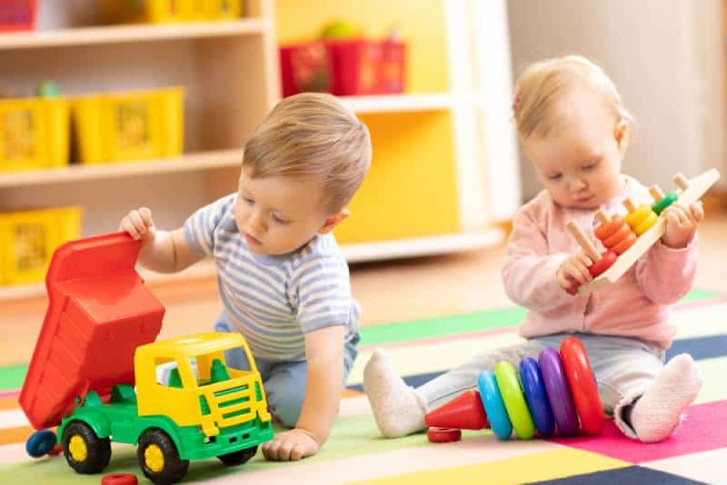 Children playing with educational toys sitting on a rug in a play room at home or kindergarten