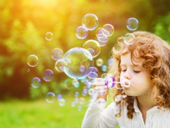Little girl blowing bubbles on the green meadow in spring time