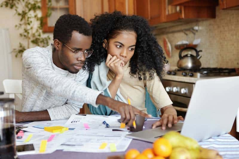 family of two sitting at table in their kitchen and paying bills online using laptop computer