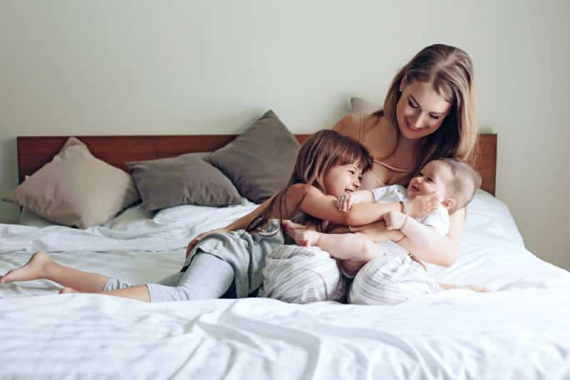 Mom with 2 kids smiling on bed in a room