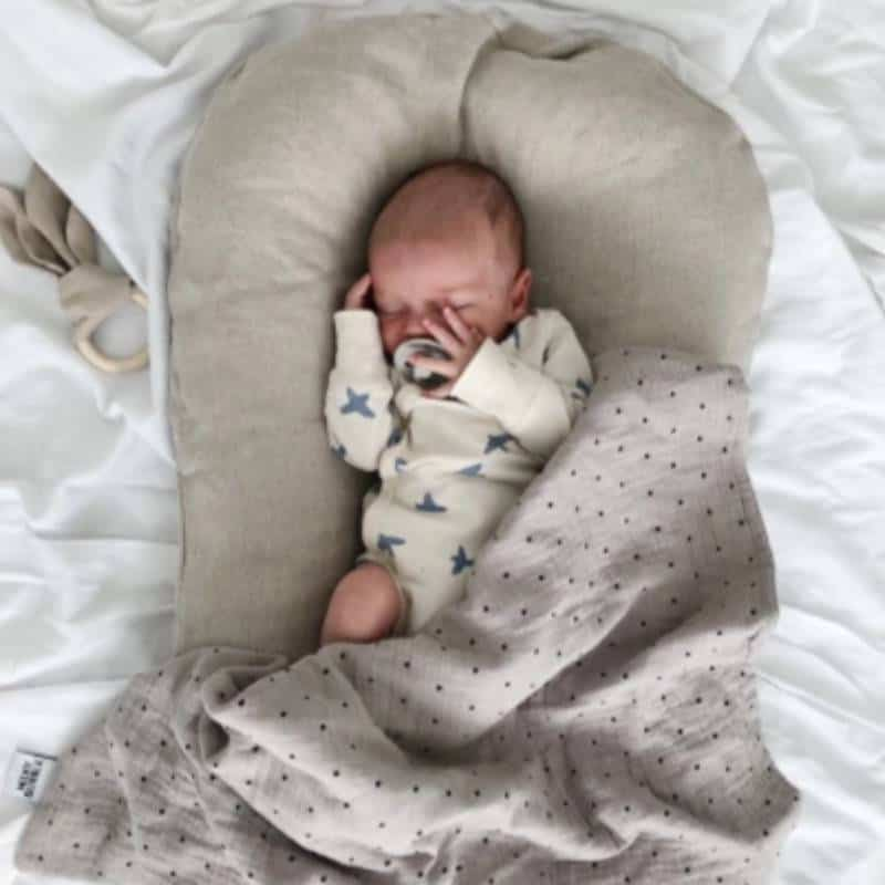 Newborn baby boy sleeping in a grey cotton baby lounger on white sheets