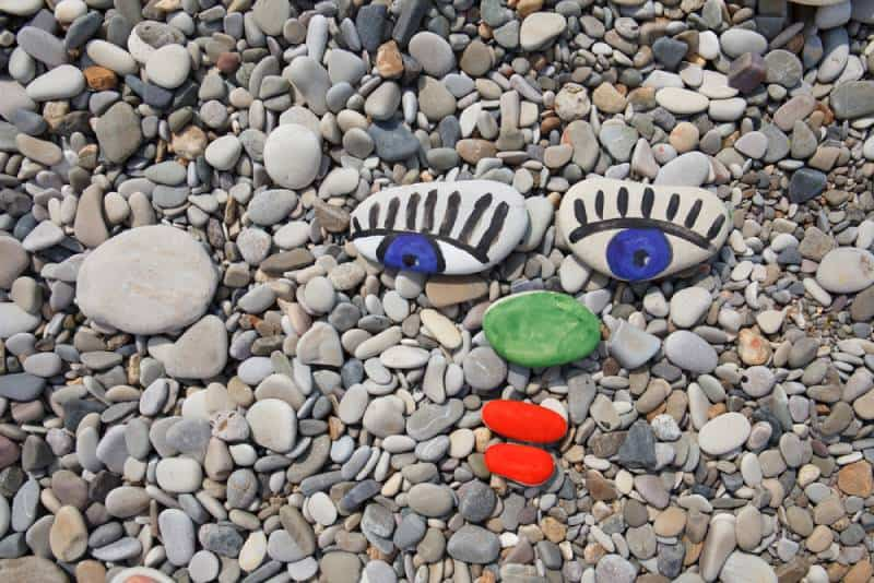 Sea smooth stones, pebbles with human face, stone painting on the beach as background