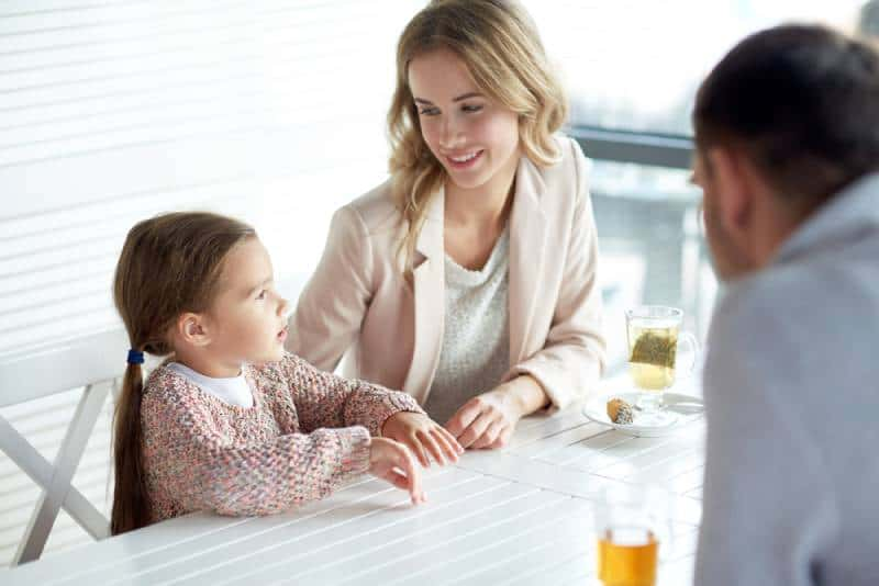 Happy mother, father and little girl having dinner and talking at restaurant