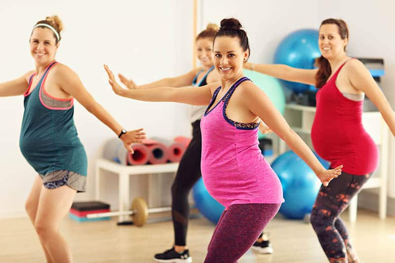 Group of pregnant women doing aerobics and dance workout classes