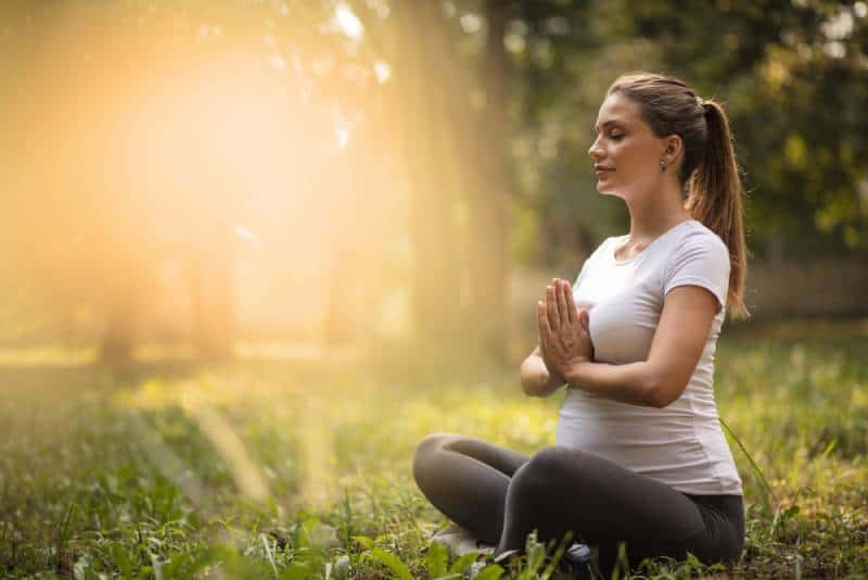 Pregnant woman meditating in nature during sunset