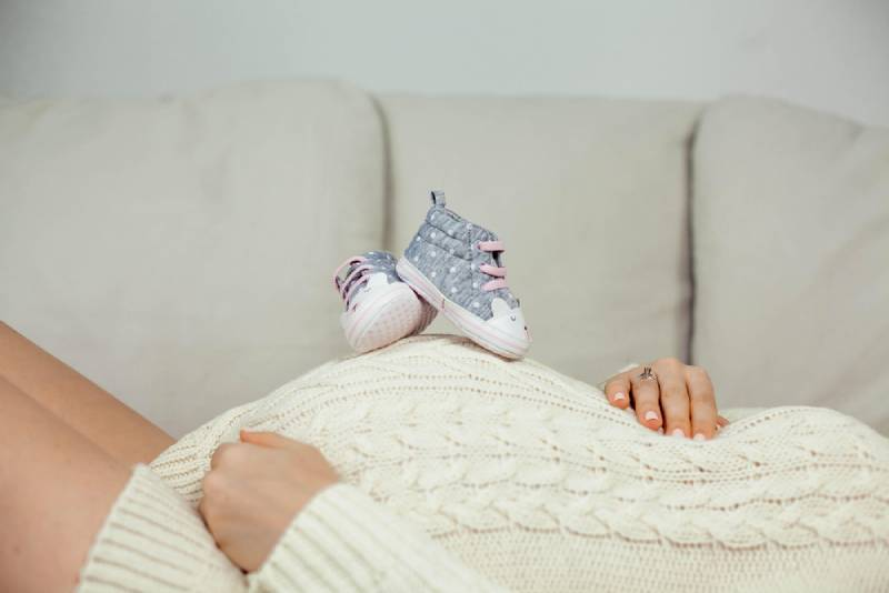 A pregnant woman in a knitted dress lies on the sofa and holds children's shoes