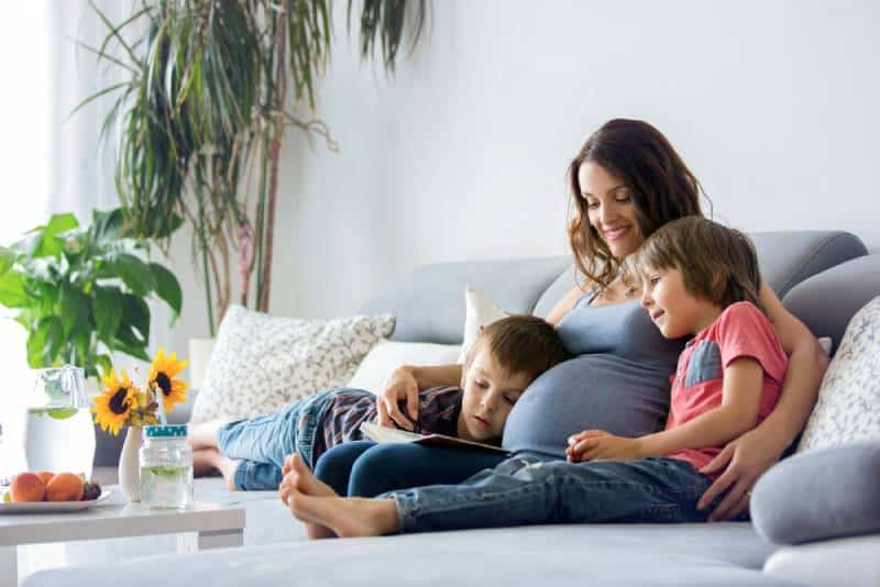 Pregnant woman, reading a book , at home to her two boys, eating fruits, hugging and laughing