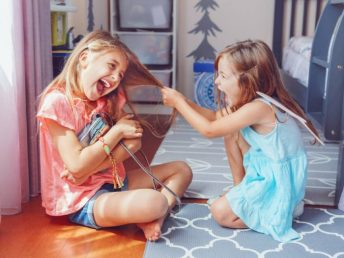 Two little angry girls sisters having fight at home over a bag