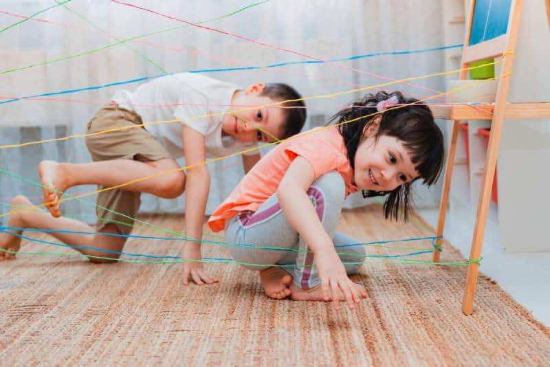 Siblings playing a rope web game and being competitive indoors