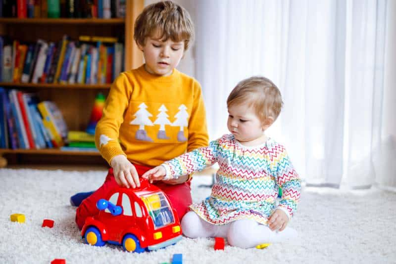 Baby girl and kid boy playing with different colorful toys at home