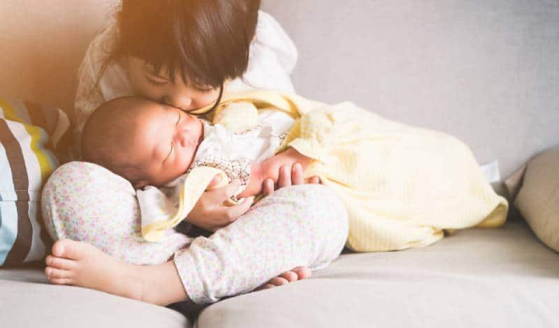 Little sister hugging and kissing her newborn brother on a sofa at home