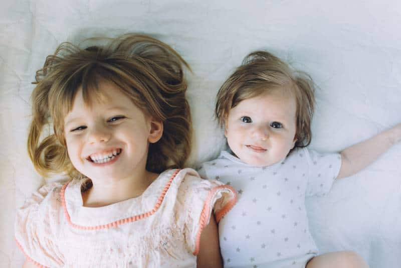 Sisters smiling while lying on bed together