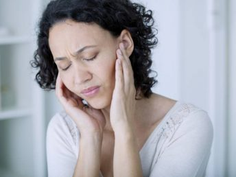 Woman in white shirt holding her ears because of pain