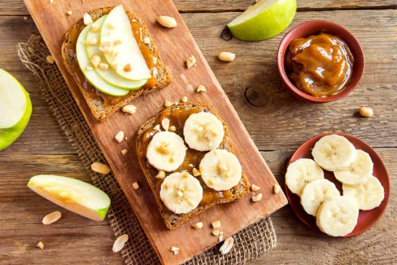 French toast with apples and bananas served on a wooden table in kitchen
