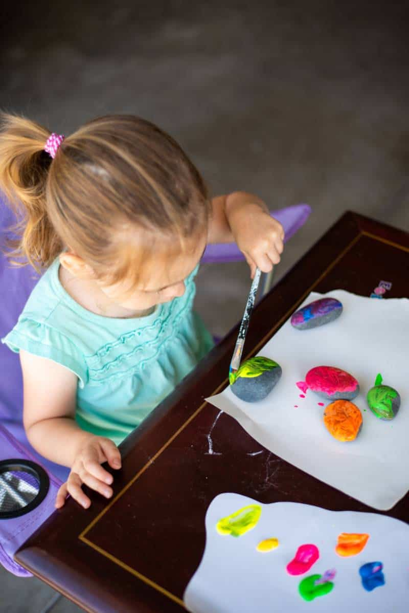 Toddler painting rocks at home