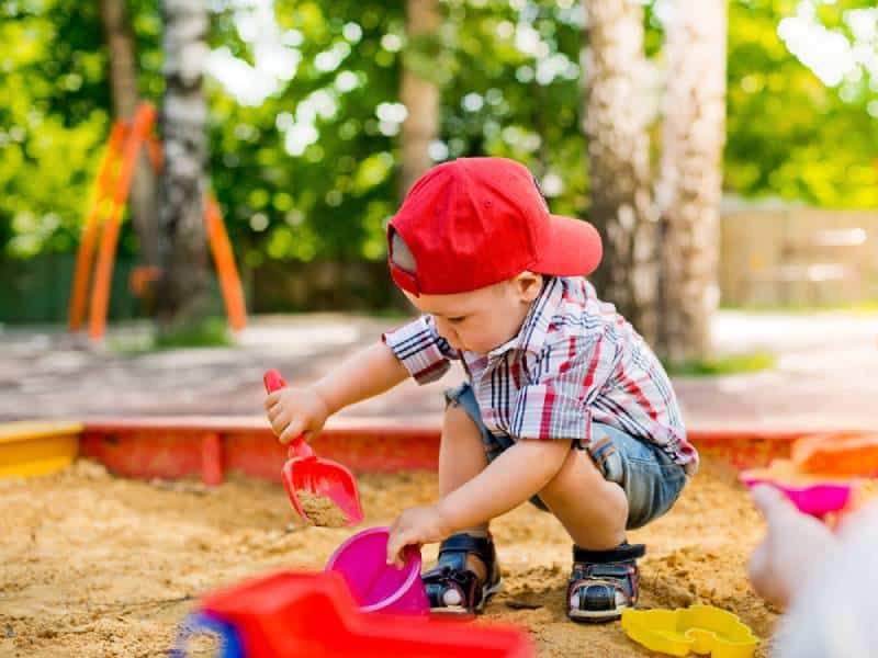 Toddler playing in sandbox with toys outdoors in summer