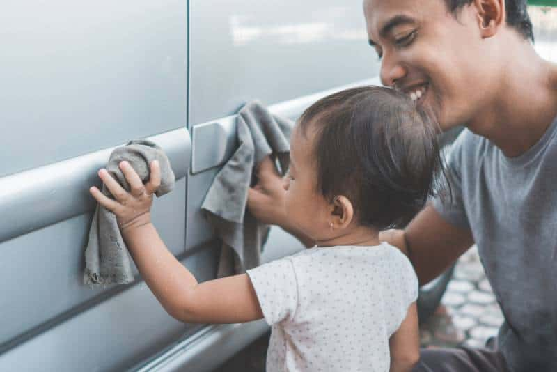 happy child being a little helper by helping her daddy cleaning up the car in summer
