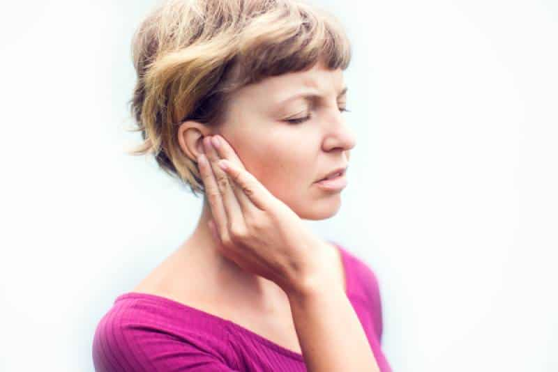 Woman in pink shirt holding her ear because of pain on white background