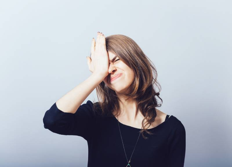 Woman in black shirt holding her head because she forgot something
