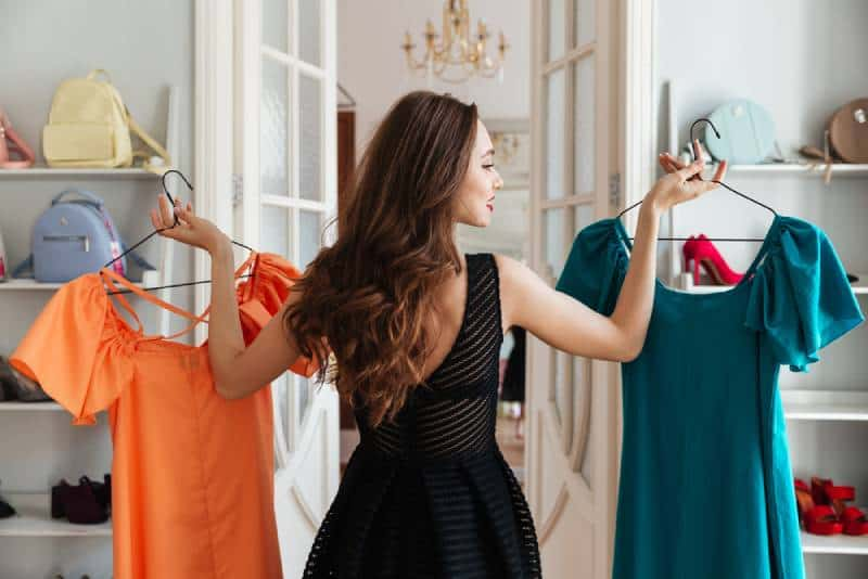 young lady standing in clothes shop indoors choosing dresses
