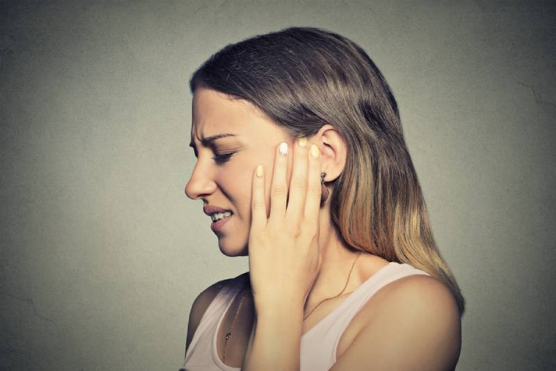 Closeup side profile sick young woman having ear pain touching her painful head isolated