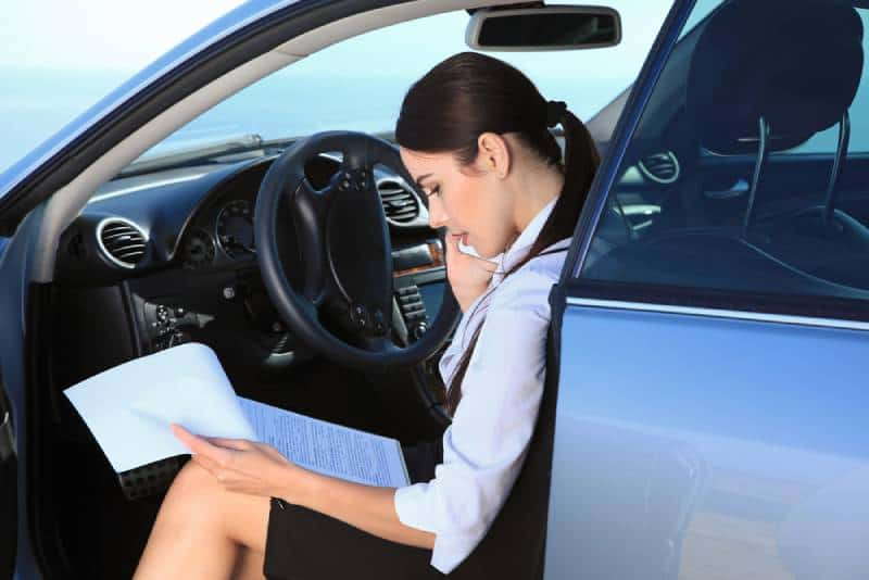 Business woman in the car examines important documents while talking on the phone