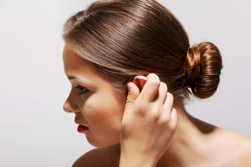 Side profile sick female having ear pain touching her painful head isolated on grey-white background