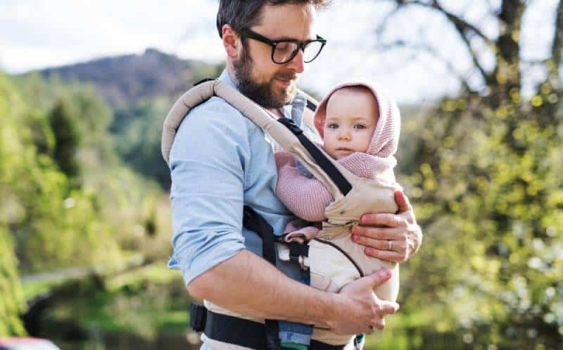 A father with his toddler daughter in a baby carrier outside on a spring walk