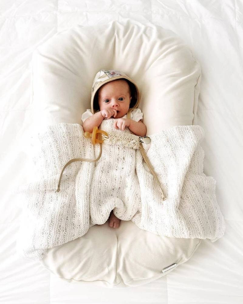 Newborn baby in a white baby lounger with a blanket on white sheets