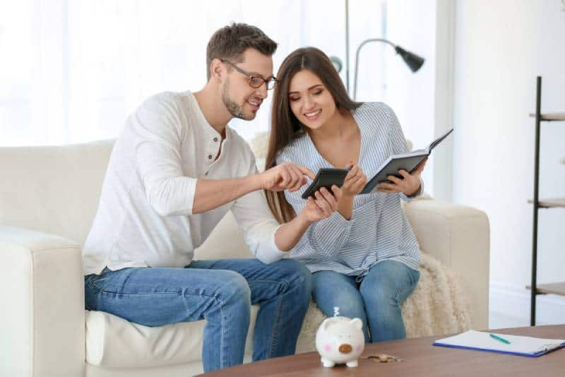 Young couple sitting at sofa in their home and thinking about saving money for future