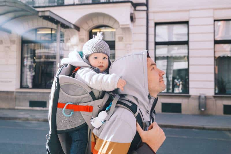 Father with child son in carrier backpack walking down the street in daytime