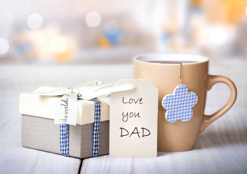 Father's day holiday greeting card with a mug on a wooden table
