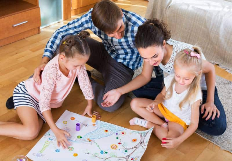 Happy young family with 2 kids playing at board game in domestic interior