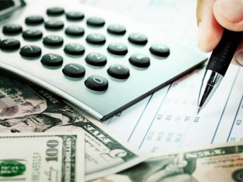 Money and checkbook with hand holding a pen, calculator on table