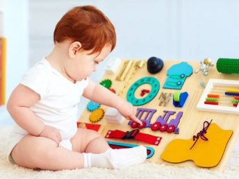 cute toddler baby in white playing with montessori toy board at home