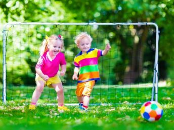 Two happy children playing football outdoors in school yard in summer